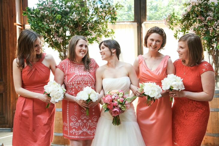 Emma let her bridesmaids have fun with their wedding day look by letting them choose their own dresses in a lively shade of coral. The diversity among their dresses played up the day's laid-back feel, while bringing a bright punch of color and personality to the ceremony.