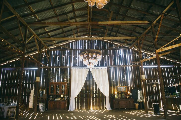The late-1800s barn features a mason jar wagon wheel chandelier.