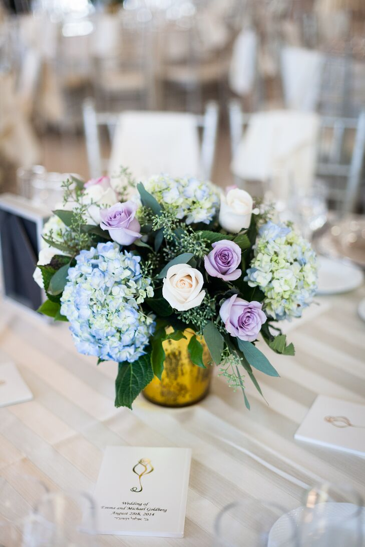 Their centerpieces had a more vintage vibe. Low arrangements of blue hydrangeas and purple and white roses filled darker gold vases on every table at the reception at Greentree Country Club in New Rochelle, New York.