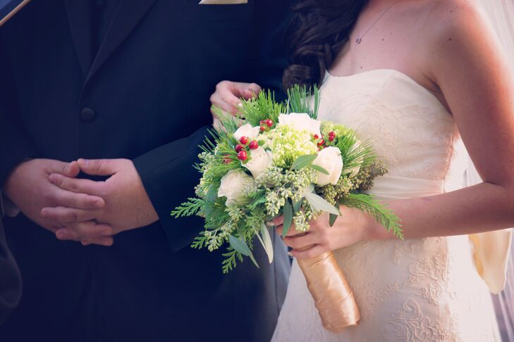 Camelia carried a holiday-inspired bouquet of pine, white roses and red hypericum berries with a gold wrap.