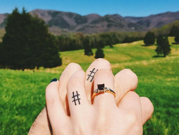 Couple with wedding ring tattoos holding hands