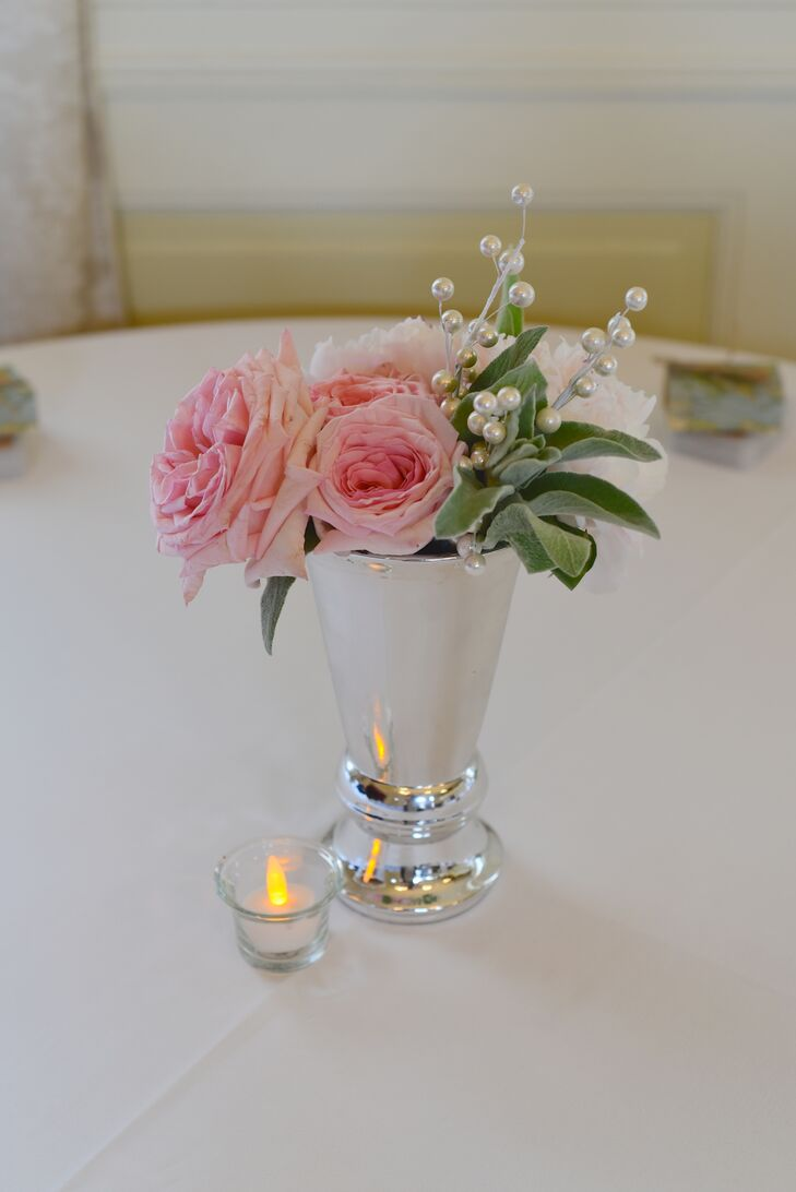 Dining tables at the reception were decorated with low silver vases that were filled with pink roses, greens and baby's breath.