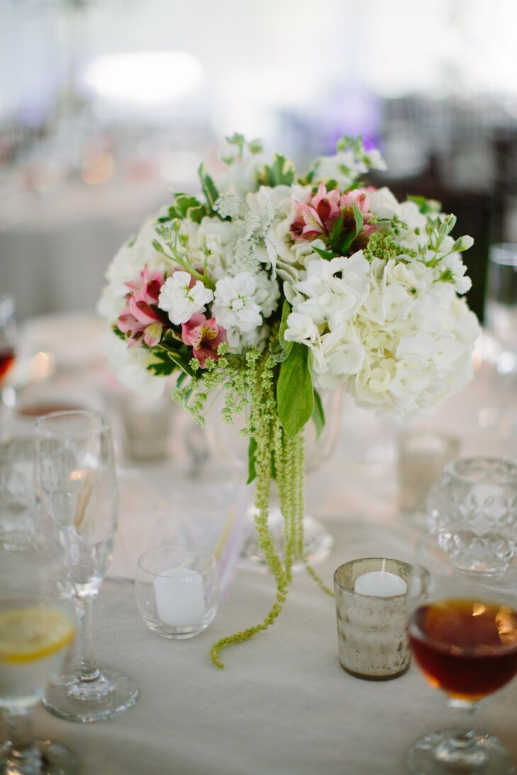 Low arrangements of hydrangeas, stock, alstroemeria and hanging amaranthus sat in clear, footed vases on the reception tables.