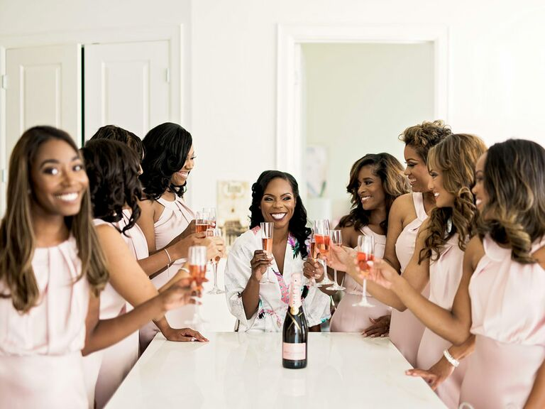 Bridesmaids toasting to bride with champagne on wedding morning