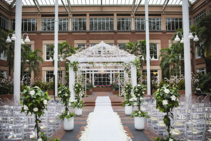 We knew that a lot of people who were unfamiliar with MEDITECH would think, 'An office building--really?' says Lauren. But I wanted the feeling of an outdoor wedding without having to worry about the weather. They took advantage of the indoor atrium--complete with a fountain, pergola and palm trees--for their sun-filled ceremony.