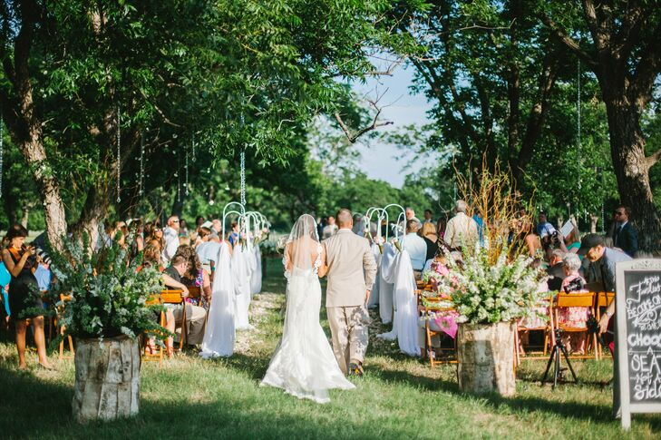 A vintage farm table and a tall wooden cross draped in grapevine and flowers served as an altar for the ceremony, which took place in a shaded pecan grove.