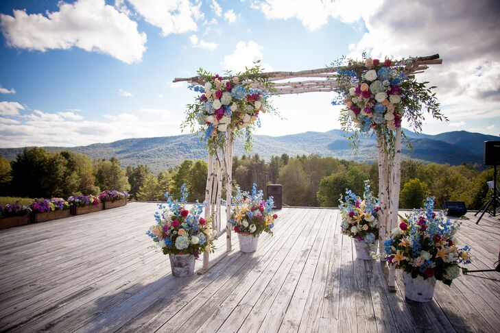The wedding arch was made of white birch branches. Lush arrangements of wildflowers decorated the top and base of the arch.
