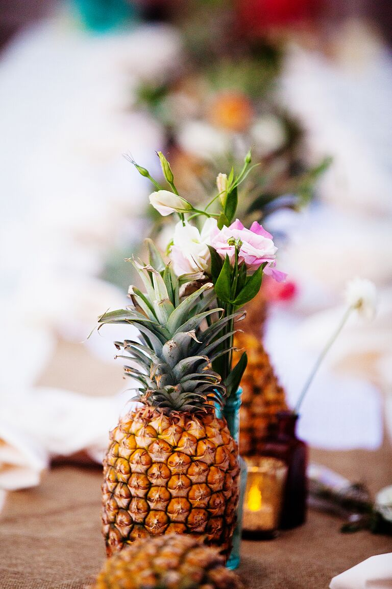Fresh pineapple and pink flower aisle decoration at outdoor wedding