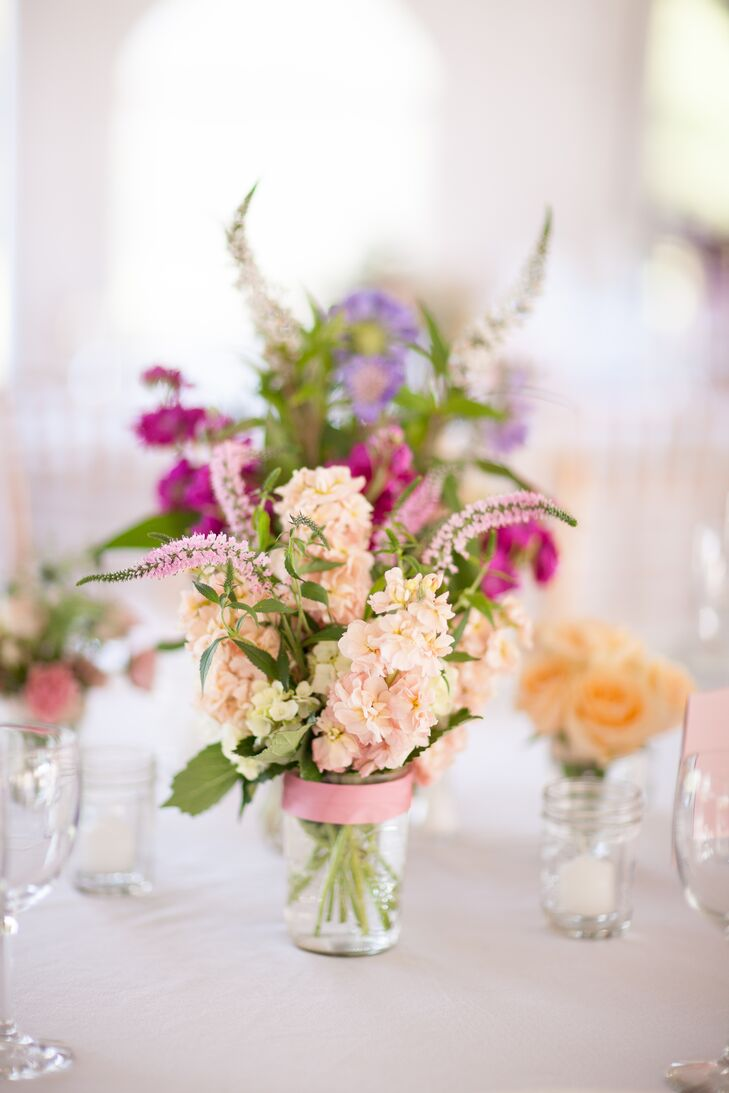 Pastel hydrangeas and veronica wildflowers were arranged in mason jars for the centerpieces. A pink satin ribbon was tied at the mouth of each jar.