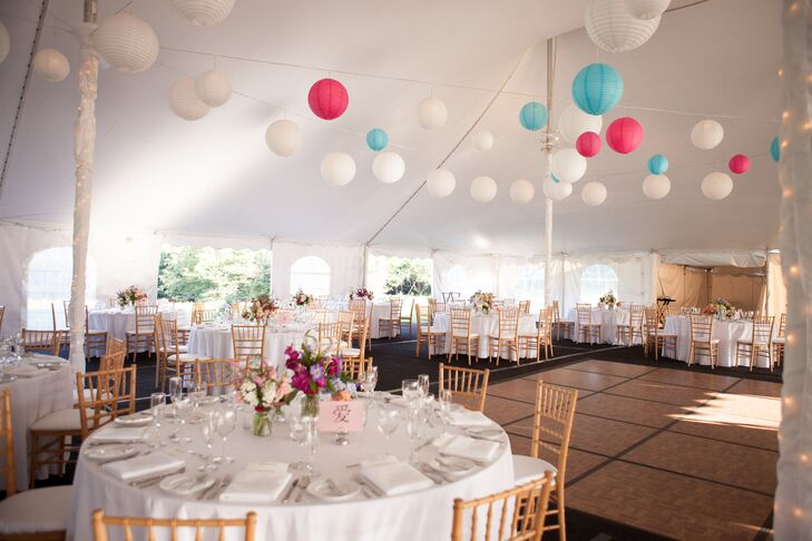 White paper lanterns complements by bright pink and blue paper lanterns hung above the round reception tables for the tented reception.