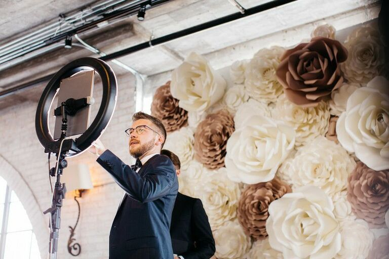 Guest taking selfie on iPad in front of faux flower wall