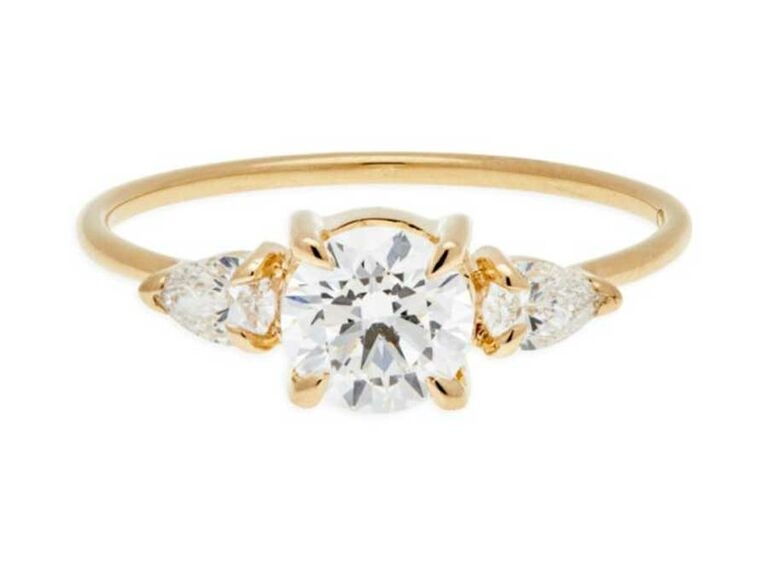 Round-cut engagement ring with pear cut side stones on yellow gold band
