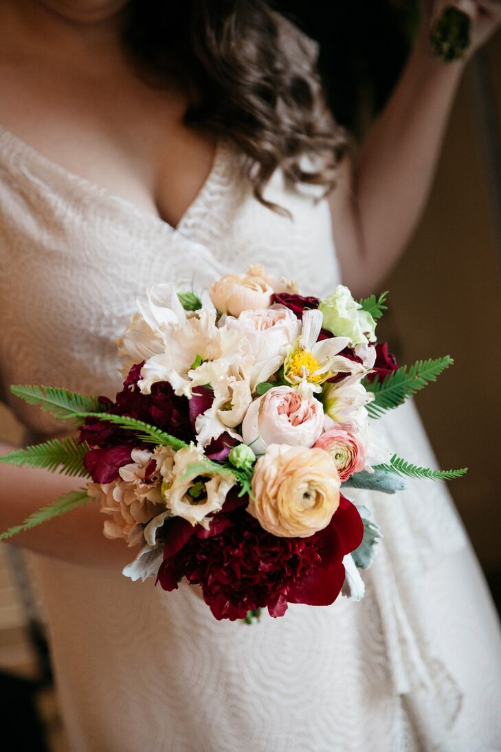 Deep oxblood blooms popped in Jessica's bouquet of ranunculus, peonies, dusty miller and ferns, along with a piece of lace from her grandmother's wedding dress.