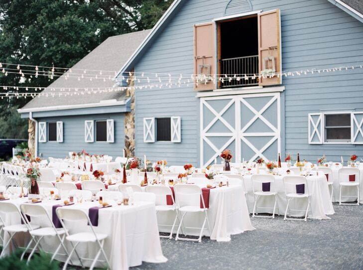 While Shelby and Zack made sure every family-style table at their outdoor reception was a little different, they kept a few staples. White linens covered every table with burgundy or plum napkins and matching vases to bring in their fall theme. White folding chairs were also paired with each place setting.
