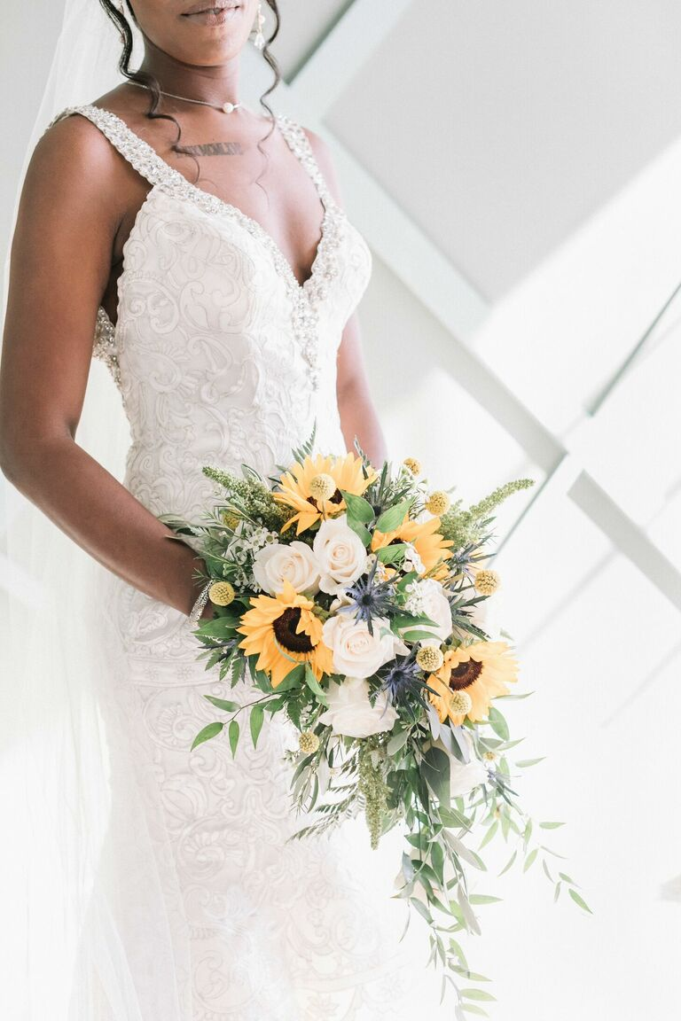 Bride holding bouquet with sunflowers and white roses