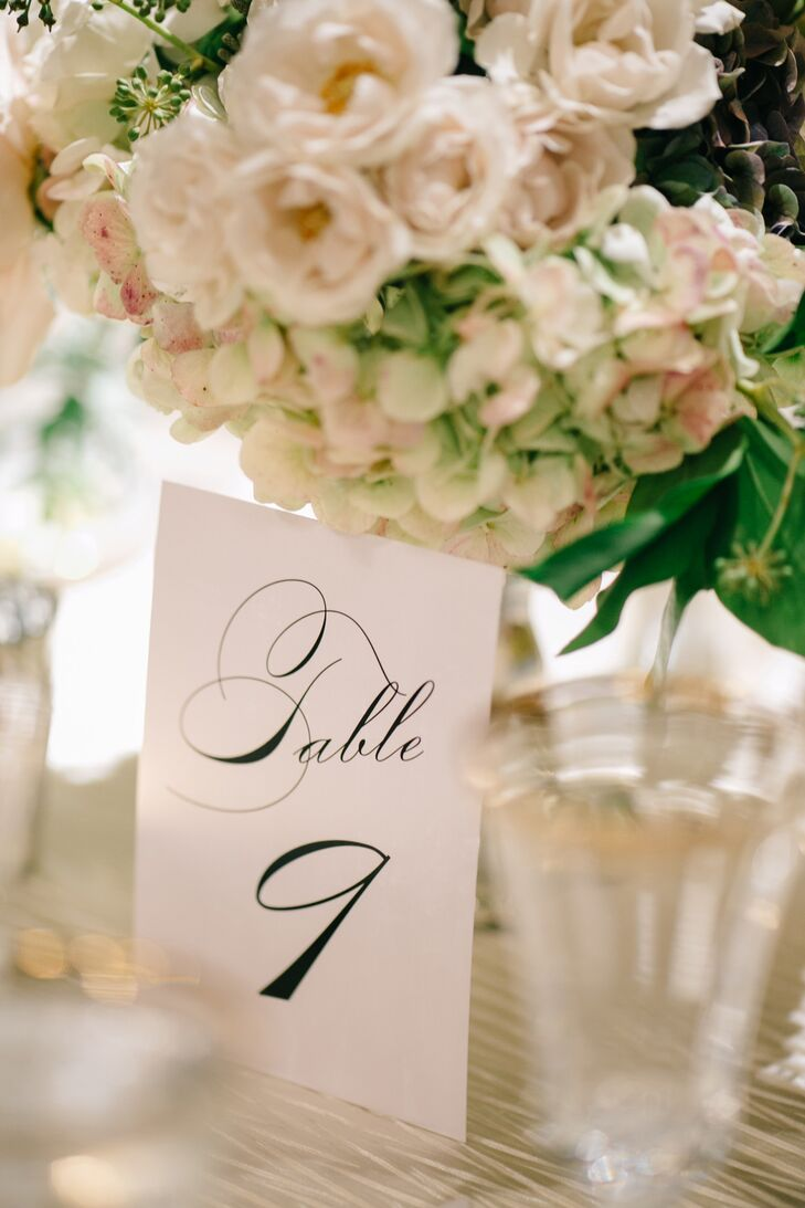 """I wanted our wedding stationery to feel elegant and simple. I always had 'The Great Gatsby' in mind,"" Marissa says. ""We went with a simple black script with gold accents."" The table numbers perfectly complemented the chic, classic wedding look. They were paired with blush and green hydrangea and rose centerpieces to complete the look."