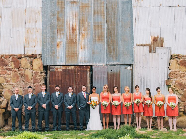 Uneven coral and charcoal wedding party lined up in front of a rusted barn.
