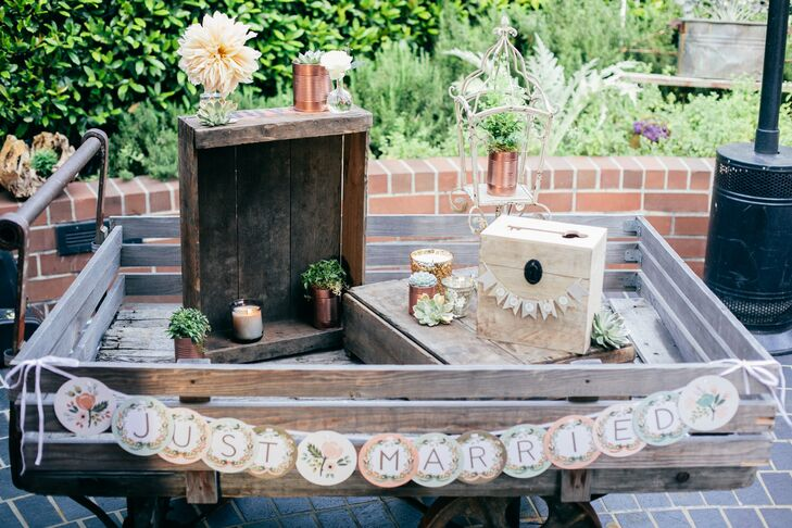 Vintage details, like this display of reclaimed wooden crates, provided unique backdrops for classic wedding day details, like the card table, while playing up the day's rustic chic theme. Succulents, rose gold tin cans and lush peach-colored blooms heightened the effect.