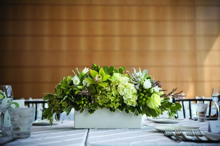 Orchids, roses, berries and fresh greens filled modern white square vases.