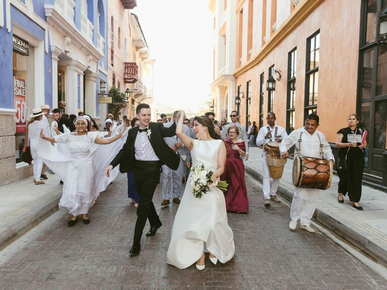 Couple walking in outdoor wedding parade with live band