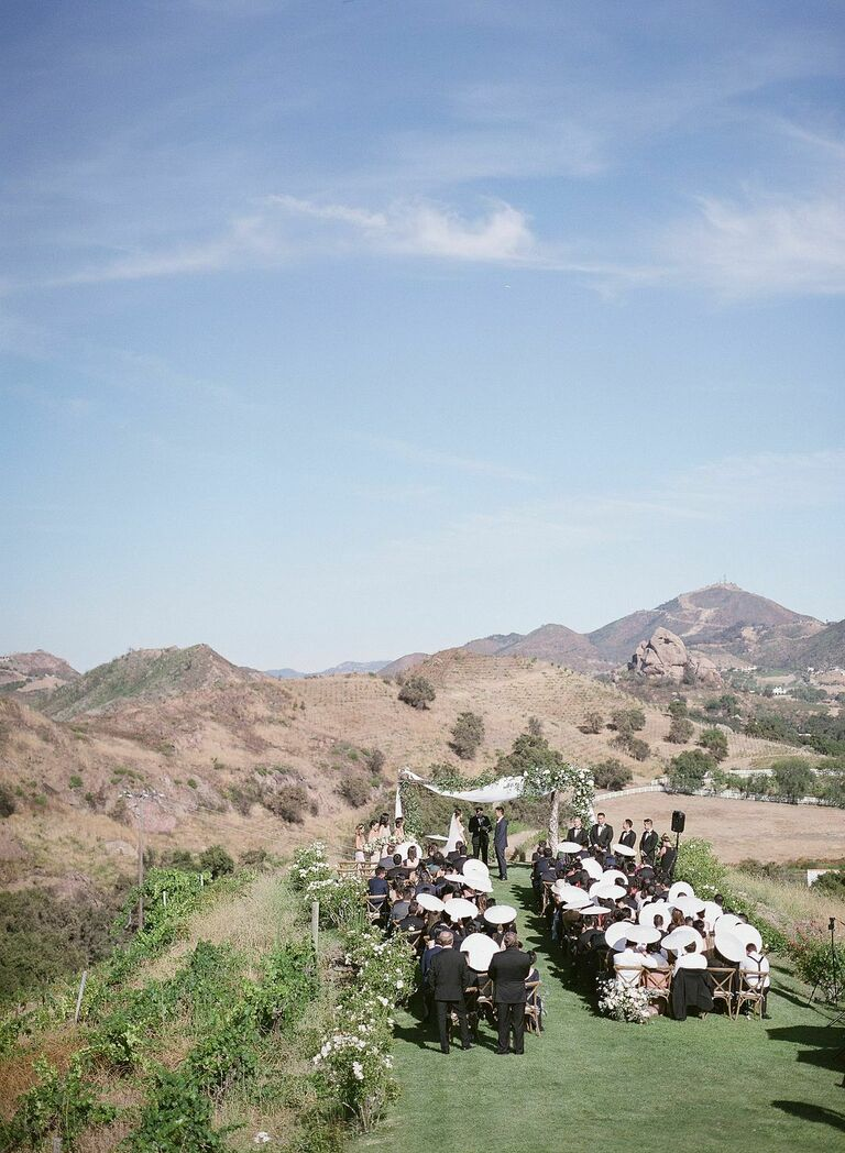 Outdoor wedding ceremony with parasols for guests