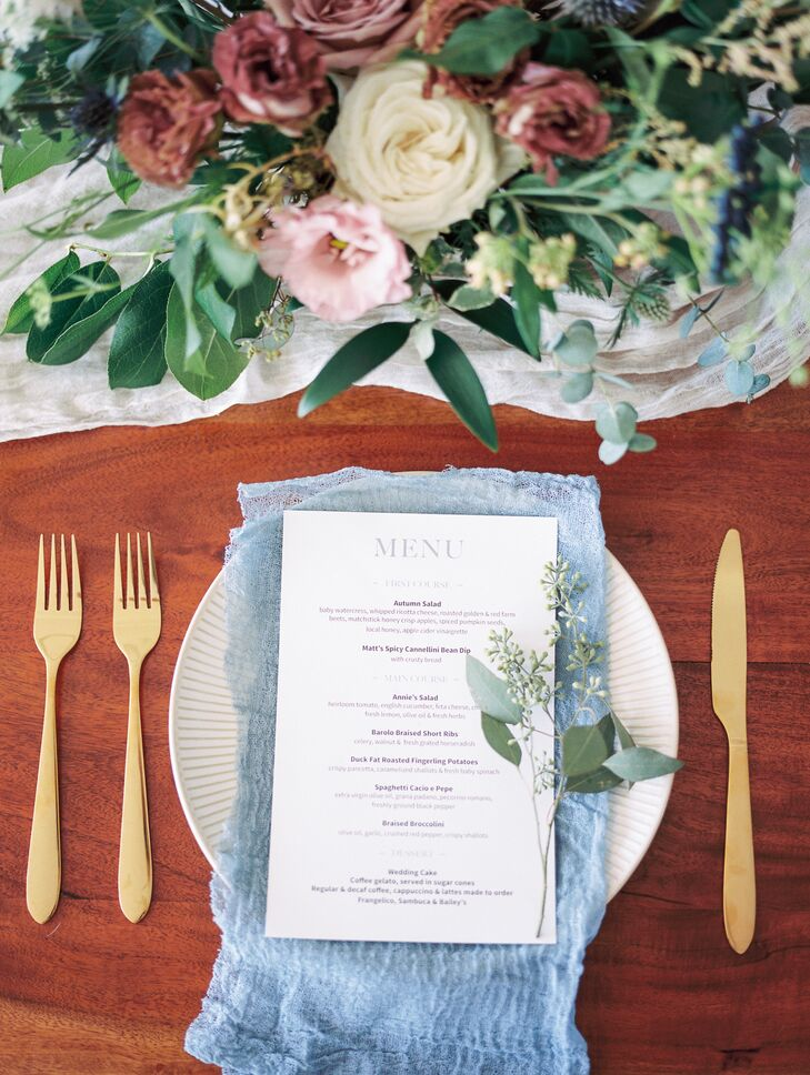 Place Setting with Blue Napkins, Gold Flatware and Menu