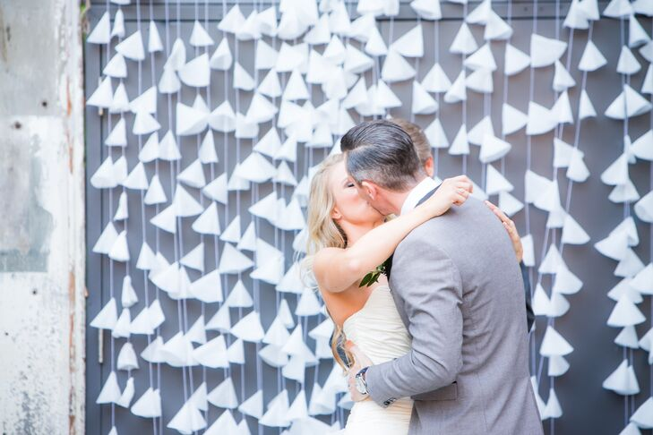 Kim and Jordan shared their first kiss with hanging white paper decorations at Strongwater Food and Spirits.