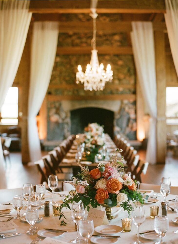 A crystal chandelier anchored the room above the long head table at Nicole and Alex's barn reception. Warm uplighting and ivory draping softened the wood and brick space and added to the romantic feel.