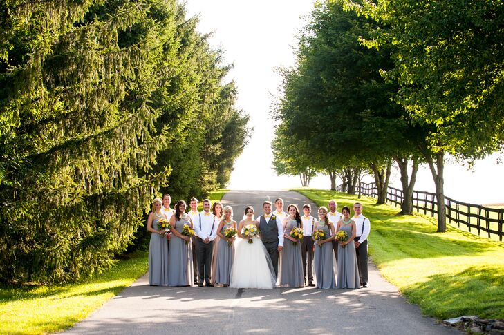 Haley and Jeremiah stood in the middle of their wedding party, dressed in different shades of gray. The groomsmen sported charcoal gray suspenders attached to their matching pants, while the bridesmaids wore heather gray floor-length dresses.