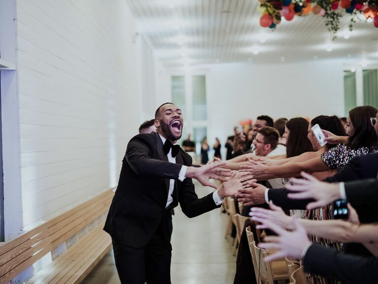 Groom entering wedding reception with high-five line