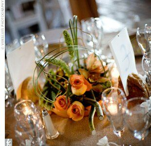 Shallow terra cotta saucers allowed for low-profile arrangements of roses accented by natural elements like eucalyptus, twigs and various grasses and greenery.