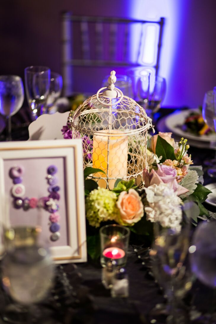 Centerpieces at the reception were made up of lanterns with candles that were surrounded by peach and lavender roses and other flowers. For a whimsical touch, the framed purple table numbers were written out in an assortment of buttons.