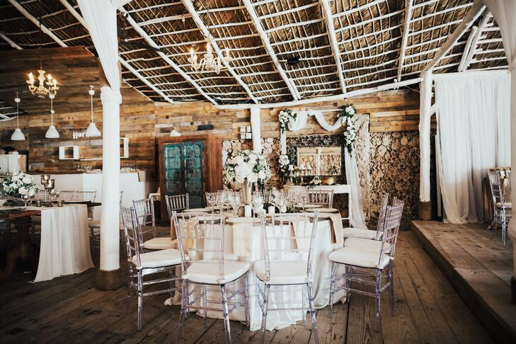 The couple's reception include a mix of round tables clad in white tablecloths and long, rustic farm tables draped in white runners that were paired with acrylic chiavari chairs. Tables were topped with white roses and gold decor.