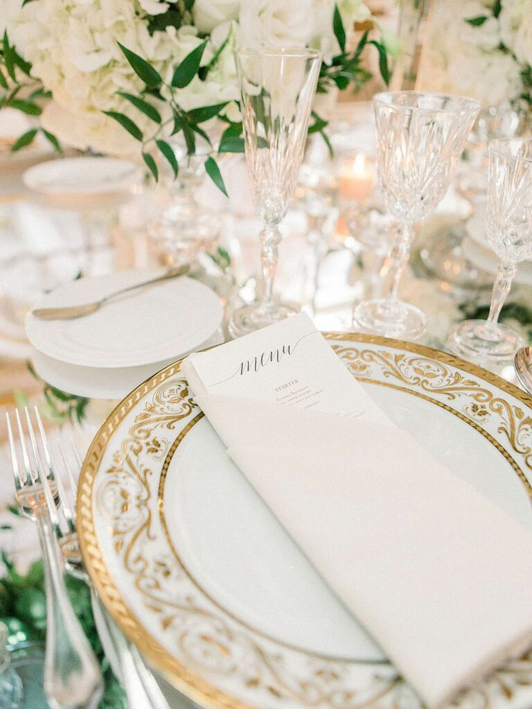 Antique gold and white table settings at elegant garden wedding