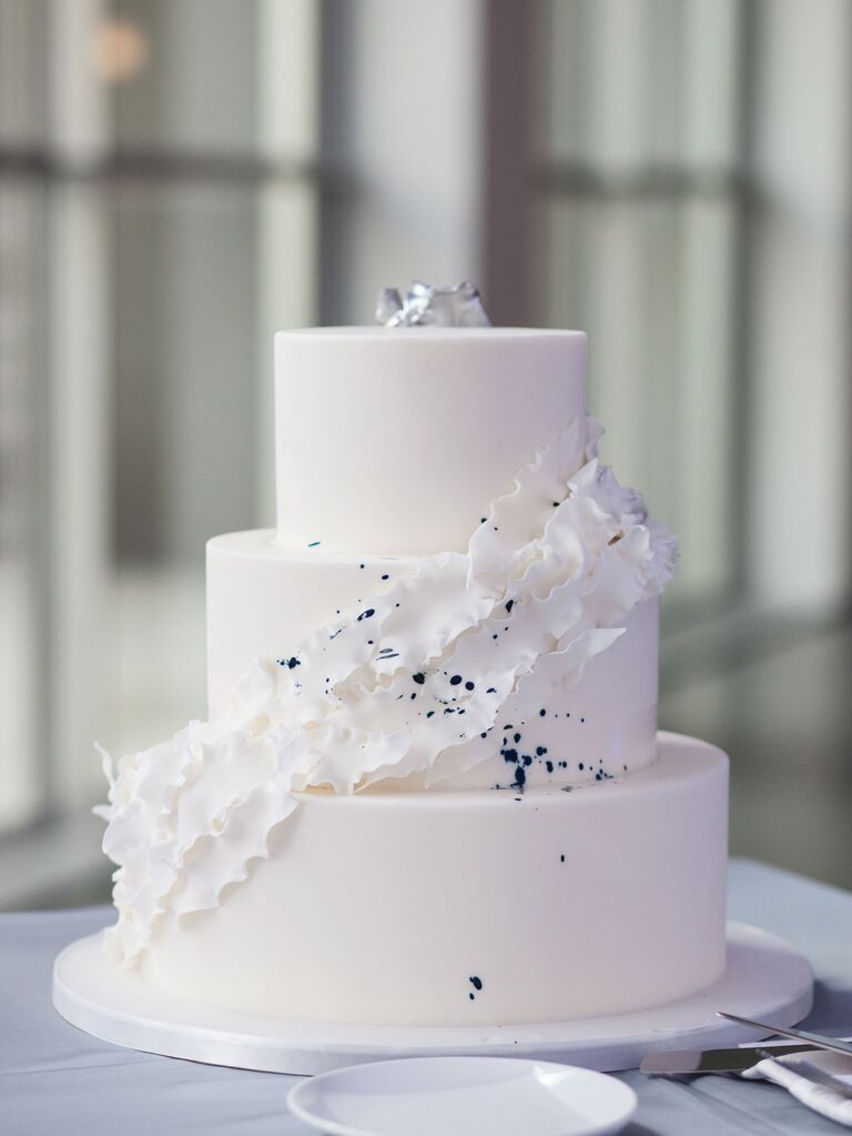 Simple three-tier white wedding cake with color splatter