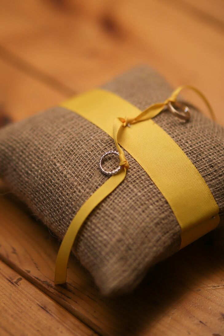 The ringbearer walked down the aisle holding a burlap ring pillow tied with yellow ribbon.