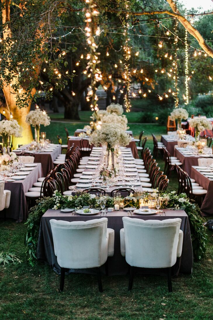 Kelly and Andrew wanted to create a feeling of casual elegance for their reception. They set long farm tables with neutral linens, bunches of baby's breath in tall cylinder vases and lush garlands. Strands of bistro lights and hanging fairy lights brought an air of whimsy to the space.