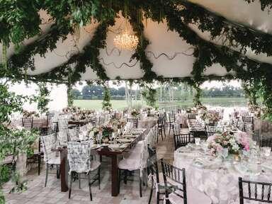 Outdoor tented wedding with green garlands