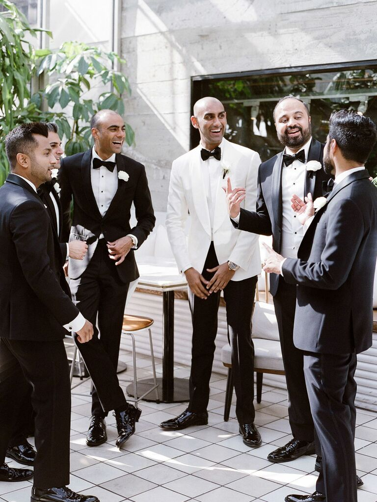 Candid photo of groom talking with groomsmen during wedding