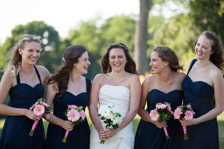 The bridesmaids wore navy dresses with a sweetheart neckline. They carried small pink gerbera daisy bouquets.