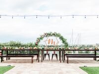 Reception with flower arch, custom sign and string lights