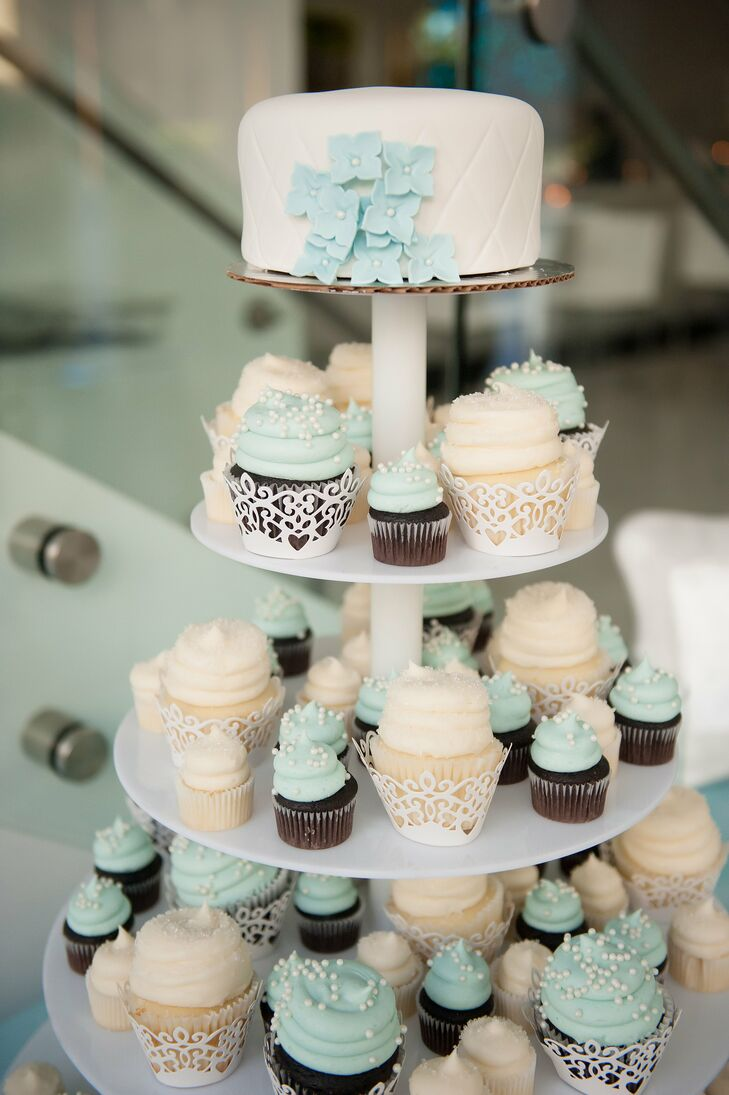 Instead of a tiered wedding cake, Brianna and Ryan had a cupcake tower with large and mini cupcakes. The cupcakes were vanilla with white frosting and sugar dust or chocolate with light aqua frosting and white pearl accents. Their single-tier cake on top had quilted ivory fondant with a few fondant aqua hydrangeas to tie in the palette.