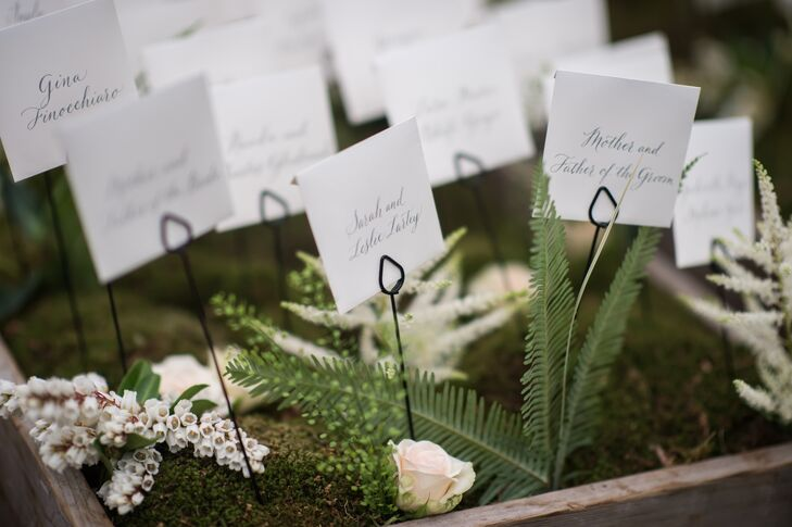 The hand-lettered escort cards were displayed on a bed of earthy green moss, white astilbes and ferns brought a rustic, organic tone to the reception table.