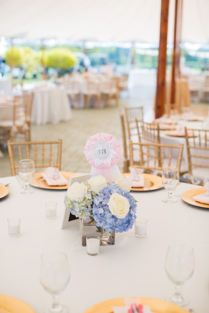 Marie of Paisley Floral Design Studios created all the floral arrangements for the wedding, drawing on the summer season and the couple's seaside-inspired palette for inspiration. Pops of brilliant blue in the form of hydrangeas dotted the tables, adding an element of vibrancy to the blush and gold tablescapes. Horse-show ribbons doubled as the table numbers and were displayed atop each arrangement, tying into the day's equestrian motif.