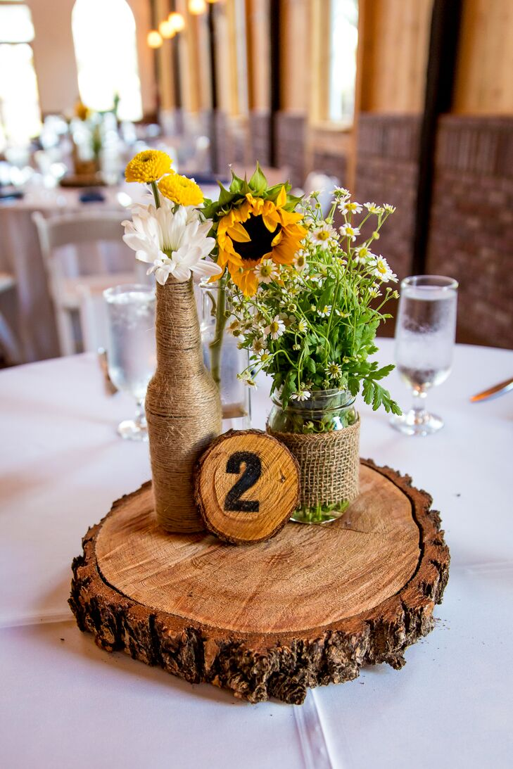 The reception tables were decorated with twine-wrapped beer bottles and mason jars filled with sunflowers, daisies and Colorado wildflowers. Unfinished wooden rounds fit the rustic theme and echoed the little wood-burned table numbers.