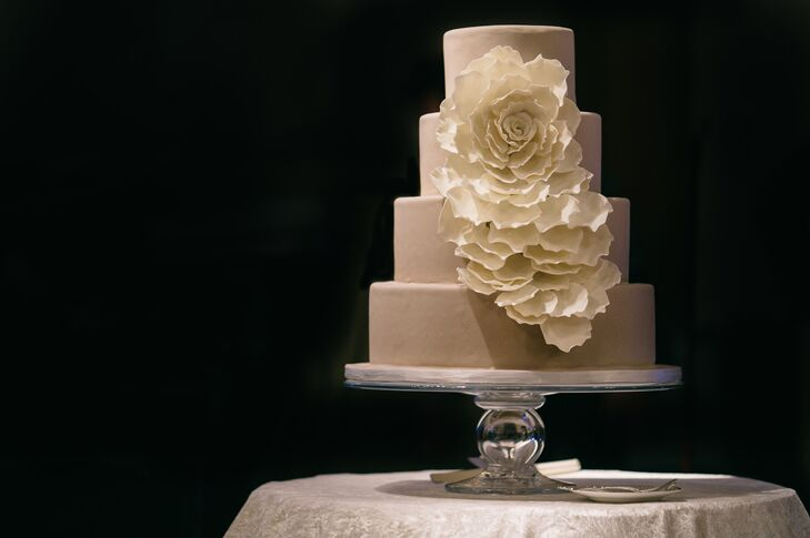 Marissa and Alex enjoyed a four-tier beige wedding cake decorated with a stunning cascading white sugar rose. Although the outside of the cake was very ornate, the inside was a classic white cake with berry filling. Marissa and Alex loved how the gorgeous cake matched their classic, elegant black-tie soiree.