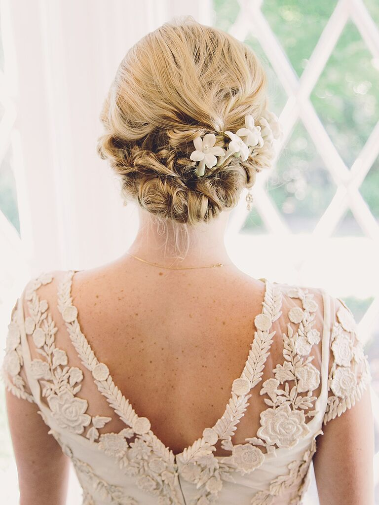 Low bun wedding hairstyle with flowers