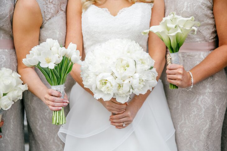 Megan and her bridesmaids each carried a white bouquet of a single variety of flower. Megan's bouquet consisted of white peonies. One maid of honor carried a bouquet of white tulips while the other carried a bouquet of white calla lilies.
