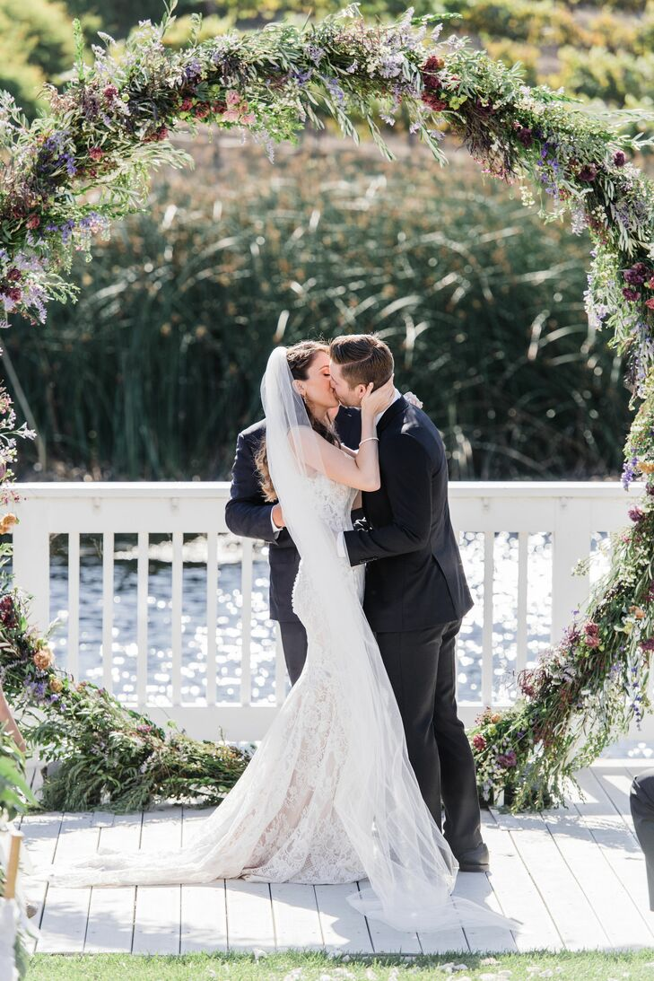 First Kiss Under Circular Greenery Wedding Arch