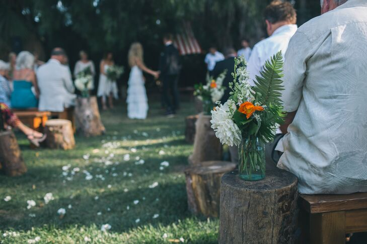 The couple placed tree stumps at the end of each aisle, topping them off with mason jars filled with white dahlias, orange poppies and ferns.